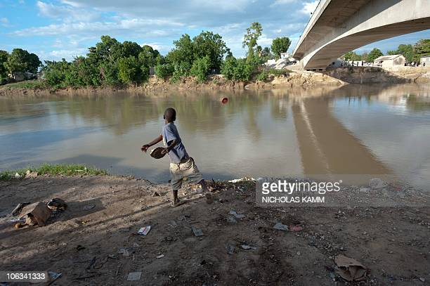A boy throws the top of a tin can into the Artibonite river whose waters are believed to be the source of Haiti's cholera outbreak at PontSonde 120km...