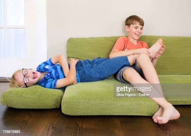 Boy Tickling Brother Feet On Sofa At Home