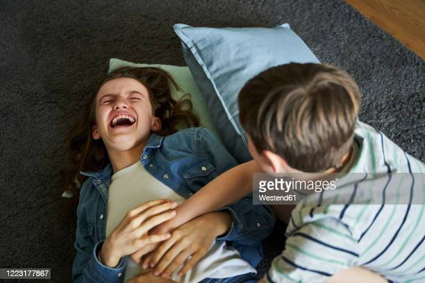 boy tickling his older sister lying on carpet at home - carpet stock pictures, royalty-free photos & images