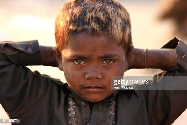 boy tied his hands behind his dyed head - pakistani boys stock photos and pictures