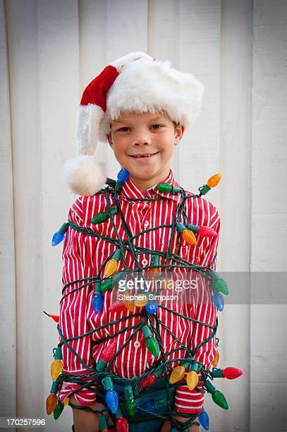 boy tied up in strings of christmas lights - junge gefesselt stock-fotos und bilder