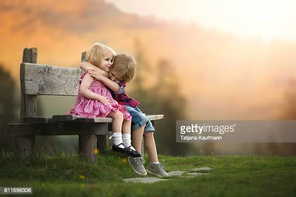 Boy tightly hugging Girl on a Bench