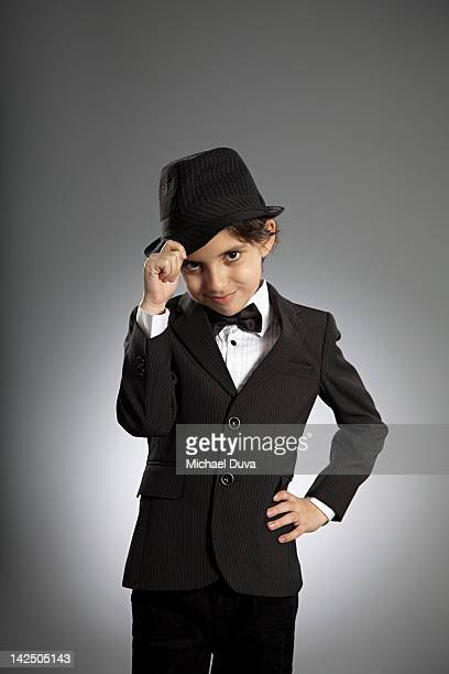 boy tipping his hat in a tuxedo suit - smoking foto e immagini stock