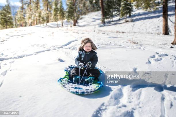 boy tobogganing in the snow - mt charleston stock photos and pictures