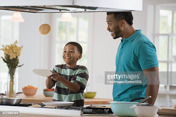Boy (10-12) tossing pancake while cooking