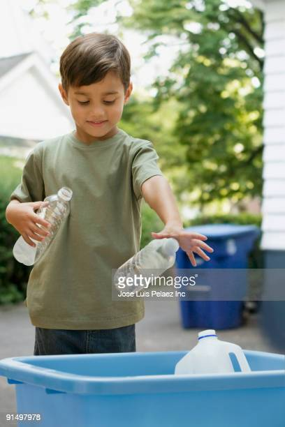 Boy tossing recyclable bottles into bin