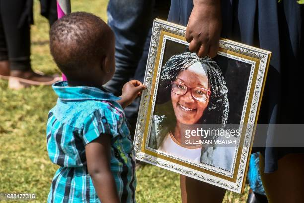 Boy touches the portrait of Trufosa Nyaboke who was among those killed during a terror attack at the Dusit hotel complex in Nairobi during her burial...