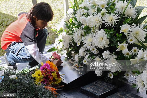 A boy touches the tombstone of Colombian drug lord Pablo Escobar at Montesacro cemetery on December 2 2010 in Medellin Antioquia department Colombia...