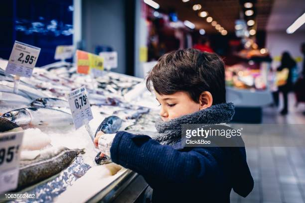 boy touching a fish in the fish market - fish love ストックフォトと画像