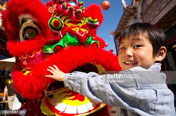 Boy (5-7) touching dragon mask at carnival, smiling, portrait