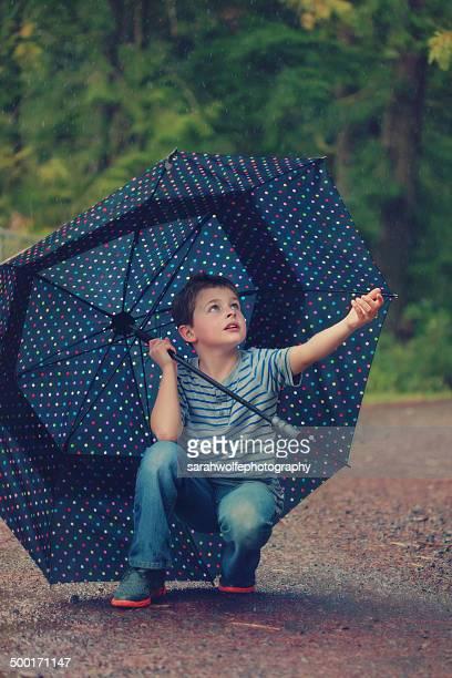 boy touching rain from under an umbrella