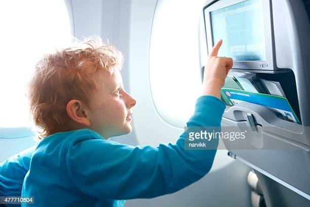 Boy touching screen of infotainment system on the airplane