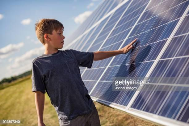 boy touching solar panels - milieukwesties stockfoto's en -beelden