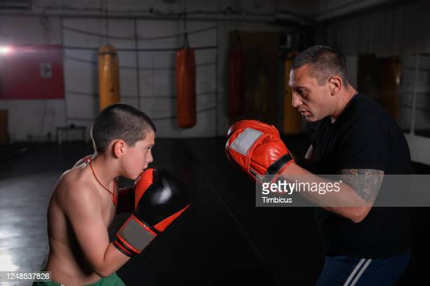 boy training kickboxing with trainer - kicking stock pictures, royalty-free photos & images