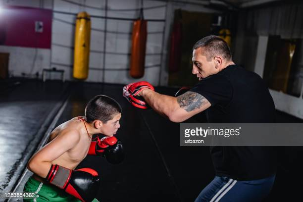 boy training kickboxing with trainer - boxing stock pictures, royalty-free photos & images
