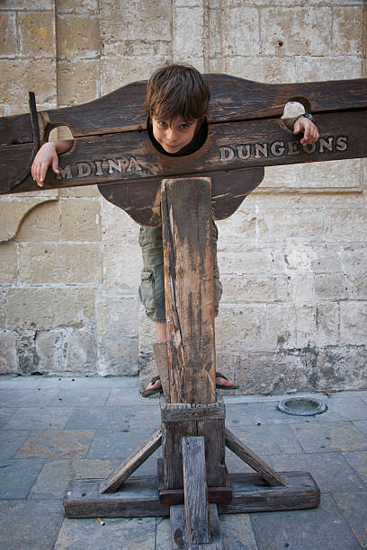 A boy trapped in a medieval torture device, Mdina, Malta