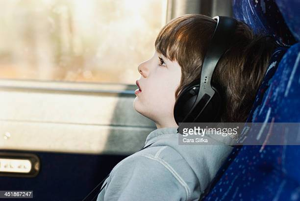 Boy traveling on a bus listens to headphones