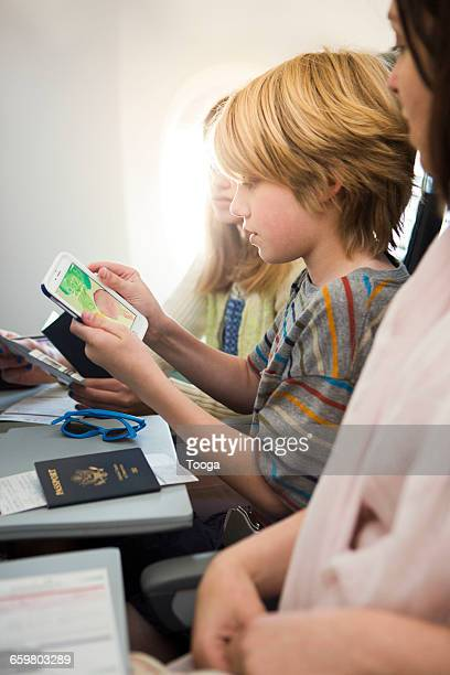 Boy traveling with family and looking at phone