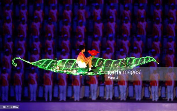 A boy travels through the air to turn off the flame during the Closing Ceremony at Haixinsha Square on day fifteen of the 16th Asian Games Guangzhou...