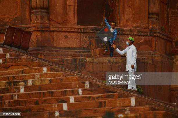 Boy tries to fly a kite outside the Jama Masjid seen deserted during Muslim's Eid-al-Fitr festival, which marks the end of the holy fasting month of...