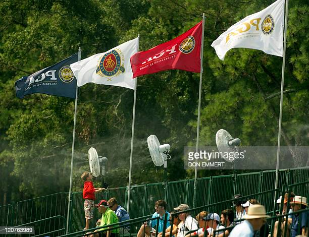A boy tries to stay cool in a fan that blows mist near the 18th green during a practice round of the 2011 PGA Championship Tournament at Atlanta...