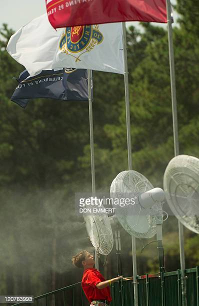 A boy tries to stay cool in a mistblowing fan near the 18th green during a practice round of the 2011 PGA Championship Tournament at Atlanta Athletic...