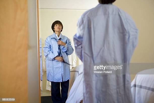 Boy trying on fathers dress shirt