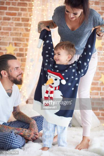 boy trying on oversized christmas sweater with parents in bed - surdimensionné photos et images de collection