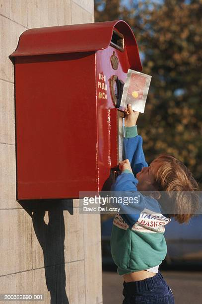 Boy (4-5) trying to drop postcard into mail box