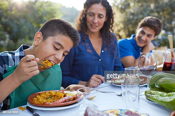 Boy trying to eat huge spoon of Paella