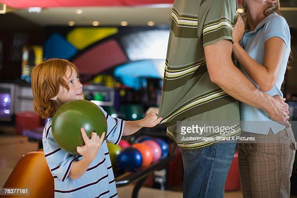 Boy trying to get his father's attention at bowling alley