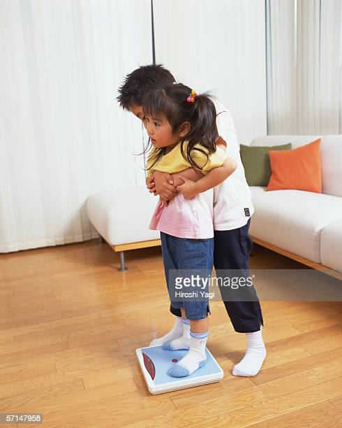 A boy trying to lift his younger sister off scale