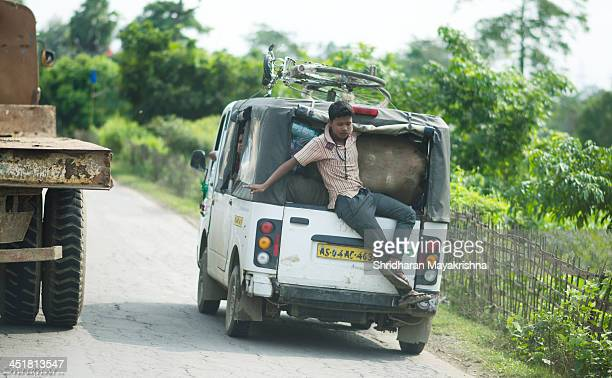 Boy trying to maintain his self balance while travelling in a Microvan used for commuting in Rural parts of the India.