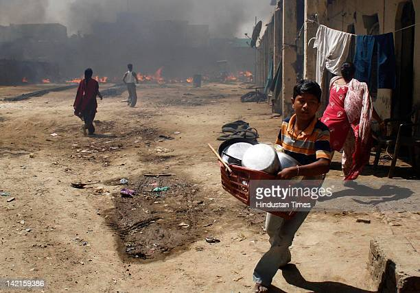 Boy trying to salvage his belongings after a fire at Navada village, Sector-62 on March 31, 2012 in Noida, India. Reportedly, two children lost their...
