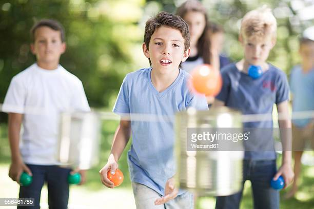 Boy trying to throw balls into tin can