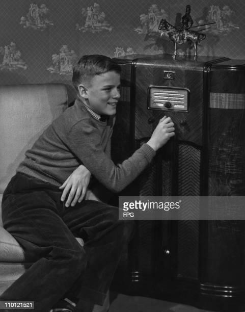 A boy tuning a large General Electric valve radio set circa 1948