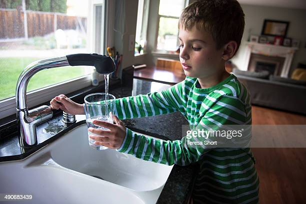 Boy Turning Off Tap After Getting Water