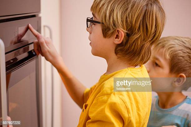 Boy turning oven on or off