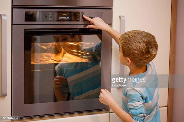 Boy turning oven on