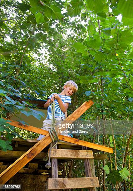 Boy tying rope to treehouse
