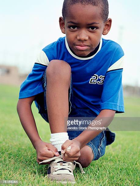 boy tying shoe - down on one knee stock pictures, royalty-free photos & images