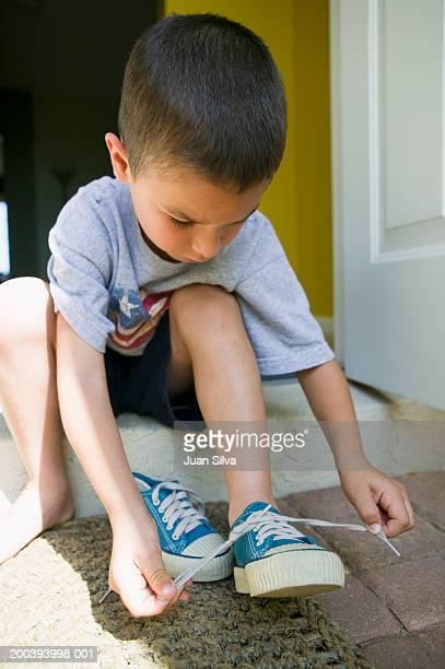 Boy (4-6) tying shoelace on doorstep, close-up