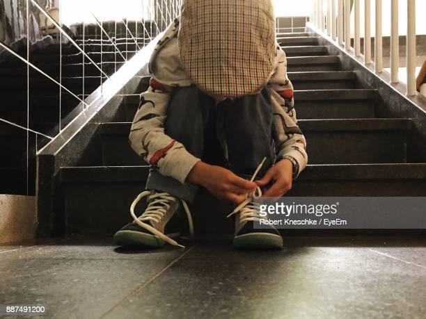 Boy Tying Shoelace While Sitting On Steps