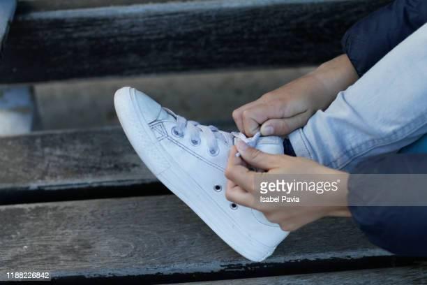 boy tying shoelaces - witte schoen stockfoto's en -beelden