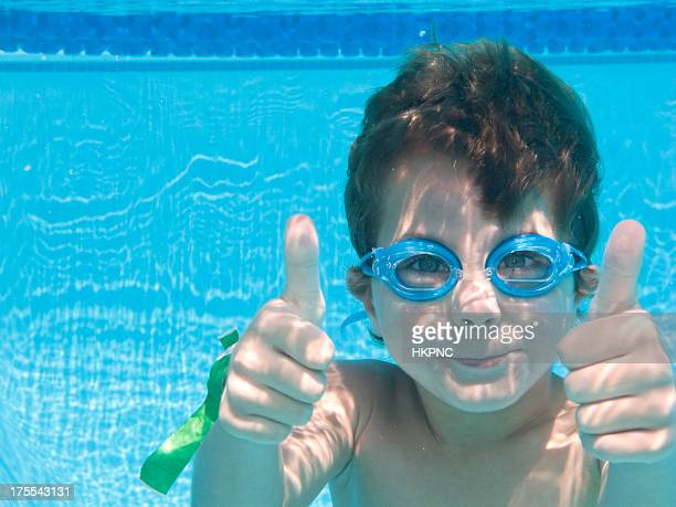 Boy Underwater In Swimming Pool With Thumbs Up.