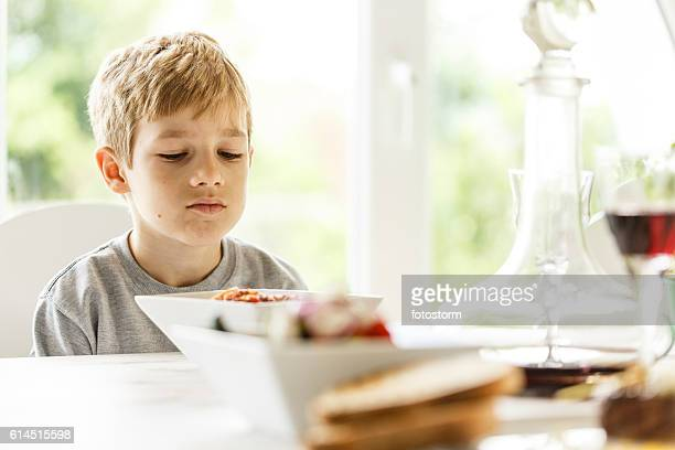 boy unhappy with his lunch - weigeren stockfoto's en -beelden