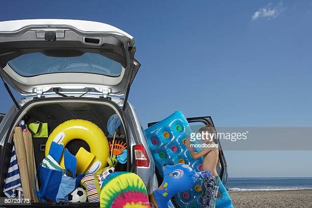 Boy (10-12) unloading air mattress from car full of beach accessories