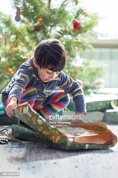 Boy unpacking Christmas present
