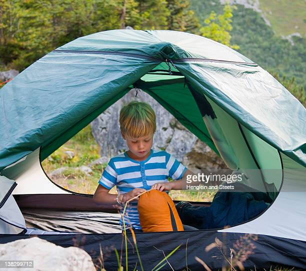 Boy unpacking sleeping bag in tent