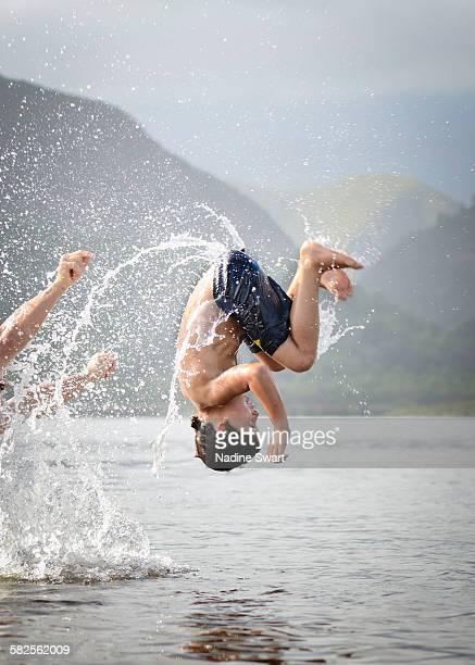 Boy upside down over water